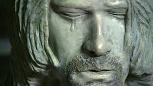 Yes, that is a single tear running down statue-Cobain's cheek.  It's meant to represent the kind of maudlin, faux- sentimentality that showed up in his music never.